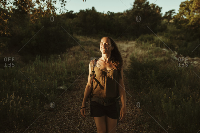 Female trekker standing in forest while sunlight falling on face during sunset