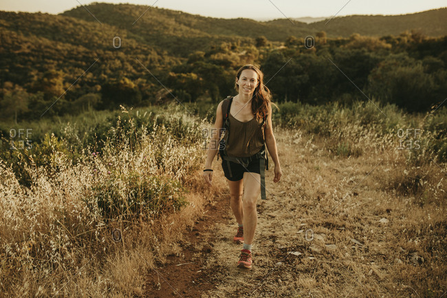 Adventurous woman walking in forest during sunset