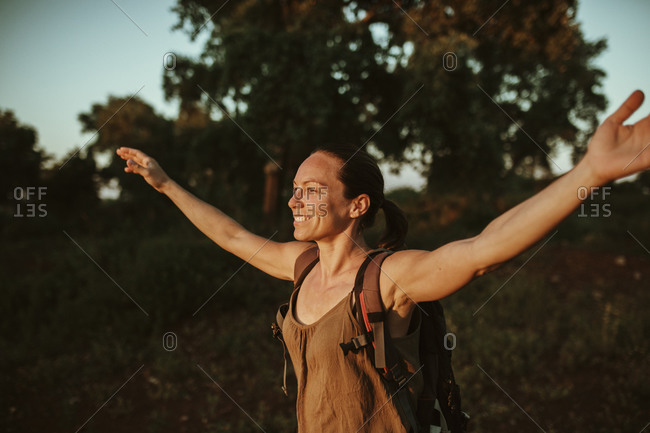 Smiling female trekker standing with arms outstretched in forest during sunset