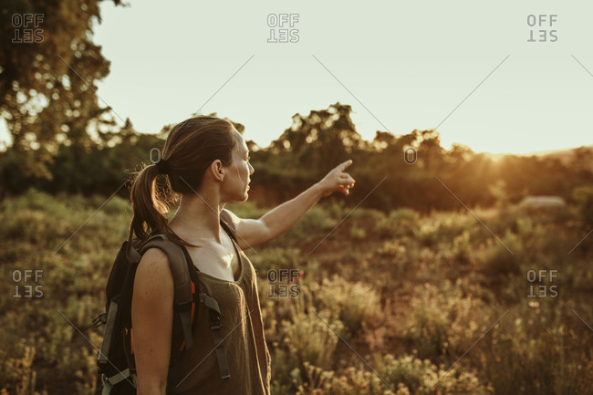 Woman trekker pointing towards sunset in forest