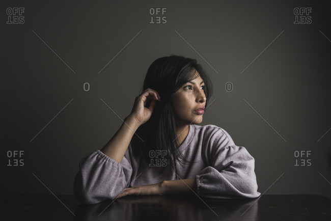 Thoughtful woman with black hair sitting at table against wall