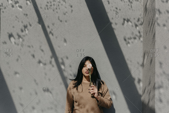 Woman holding flower in front of eye while standing against concrete wall on sunny day