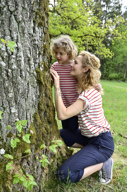 Mother and daughter looking at bark of tree in forest