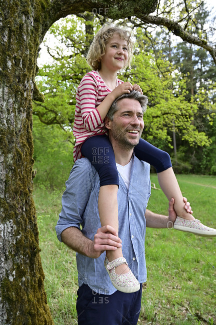 Smiling father carrying daughter on shoulder while exploring forest