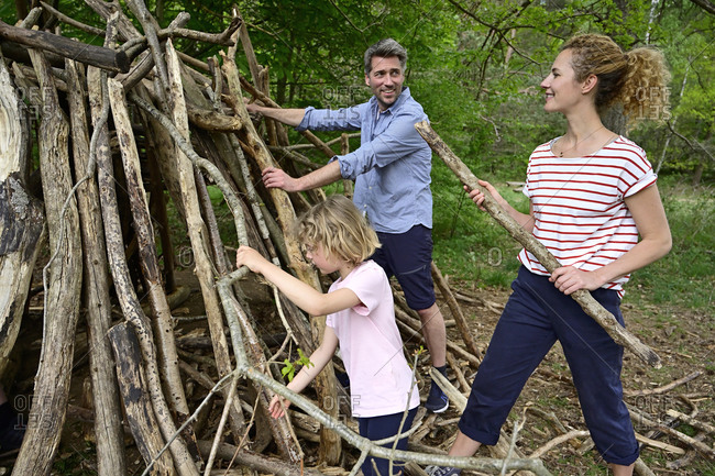 Man looking at woman while building camp with log in forest