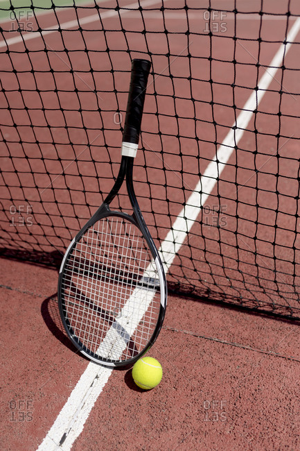Tennis racket with ball by net in court during sunny day
