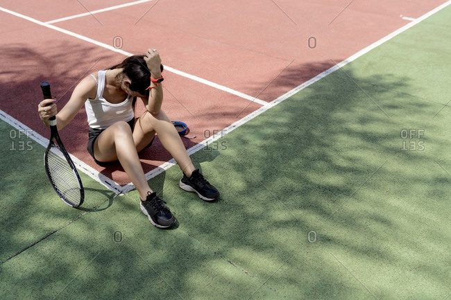Sad female tennis player sitting on floor in sports court