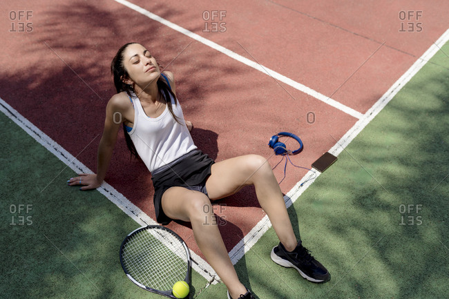 Female tennis player with eyes closed relaxing on floor in sports court