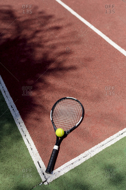 Tennis ball with racket on floor in sports court