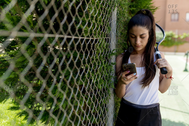 Female tennis player using smart phone while standing by fence in court