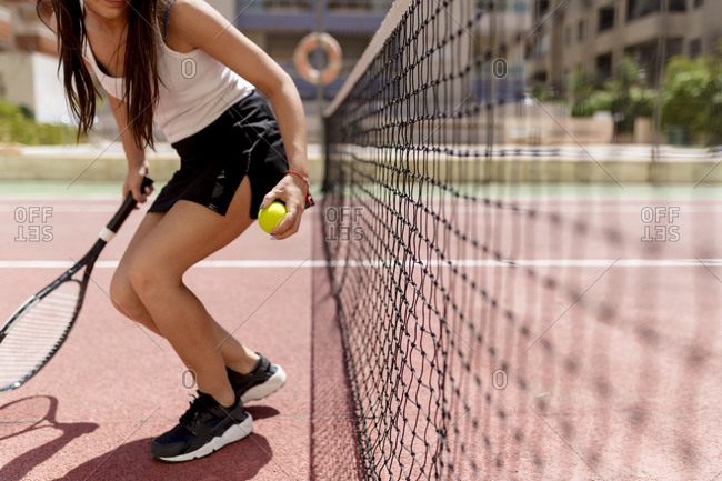 Female tennis player holding racket and ball while standing by net in court