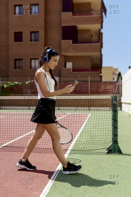 Female tennis player wearing headphones using smart phone while walking in court