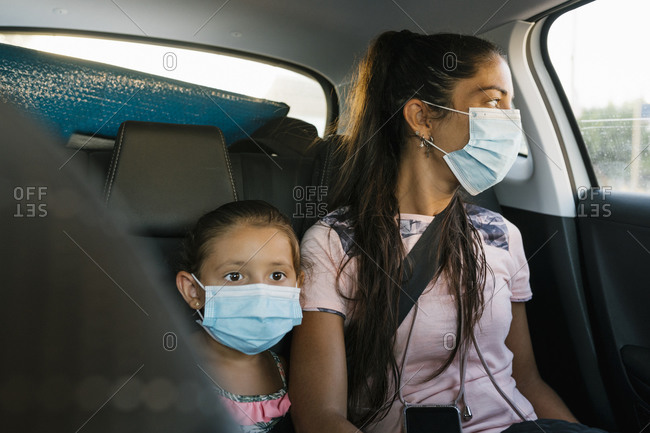 Mother and daughter with face mask sitting at back seat of car