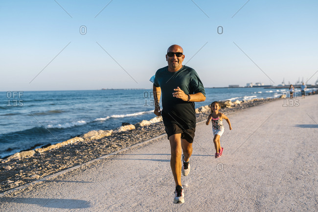 Girl running behind grandfather on road by sea