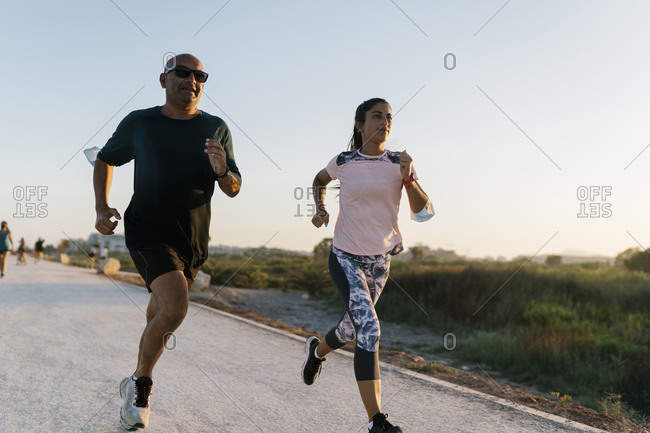 Woman running with senior sportsman on road during sunset