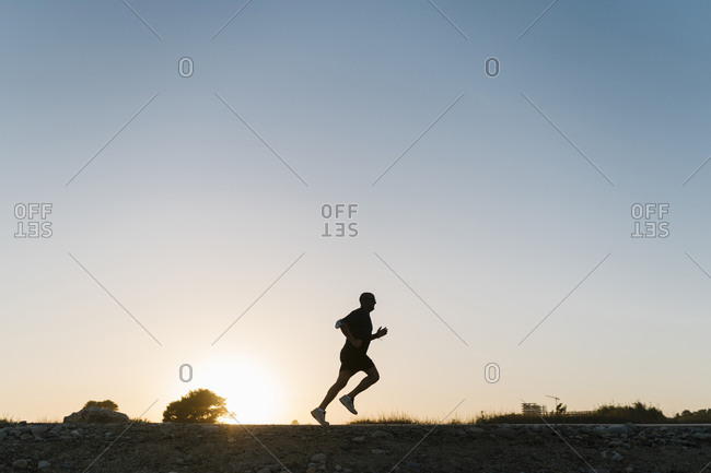 Silhouette of senior athlete jogging against clear sky during sunset