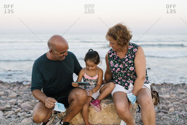 Grandparents sitting by granddaughter on rock against sea