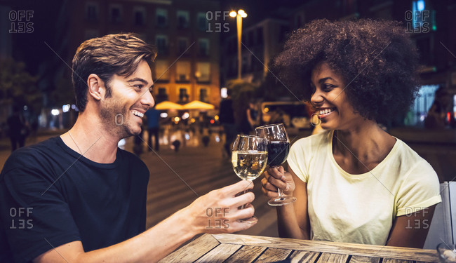 Cheerful couple looking at each other while toasting wineglasses at date night