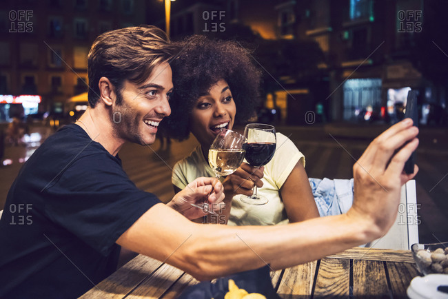 Man taking selfie with girlfriend while toasting wine with her at date night