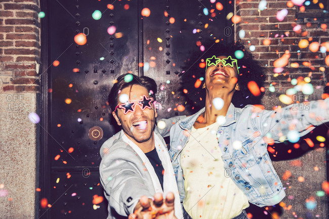 Confetti falling on cheerful couple wearing star shaped sunglasses enjoying outdoors at night