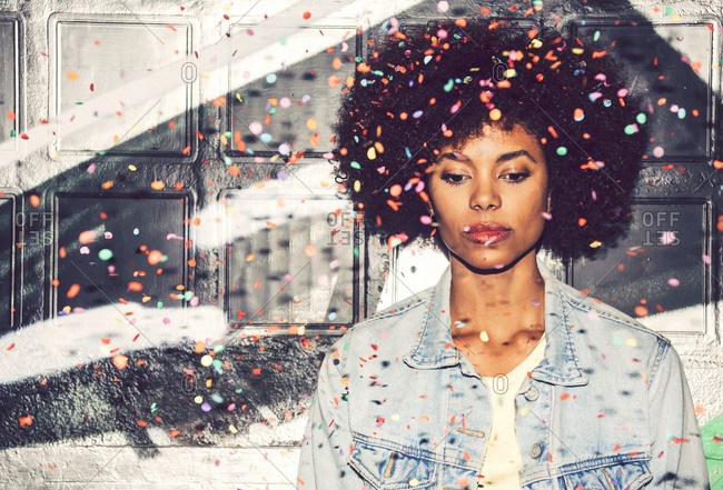 Confetti falling on thoughtful woman looking down while standing against wall