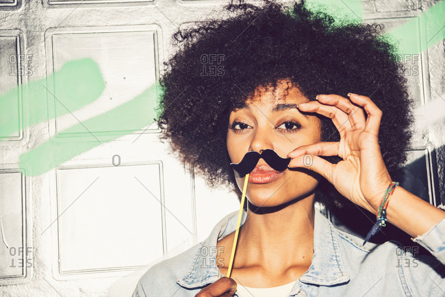 Close-up of woman with curly hair holding fake mustache on face against wall at night