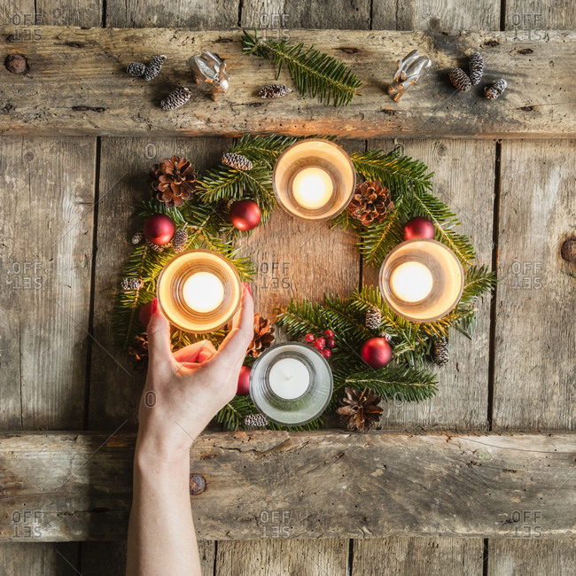 Hand of woman touching glass cover of candle burning on Advent wreath