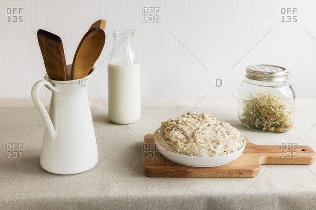 Jug with wooden spoon and spatula- milk bottle- jar of sprouts and dough on cutting board