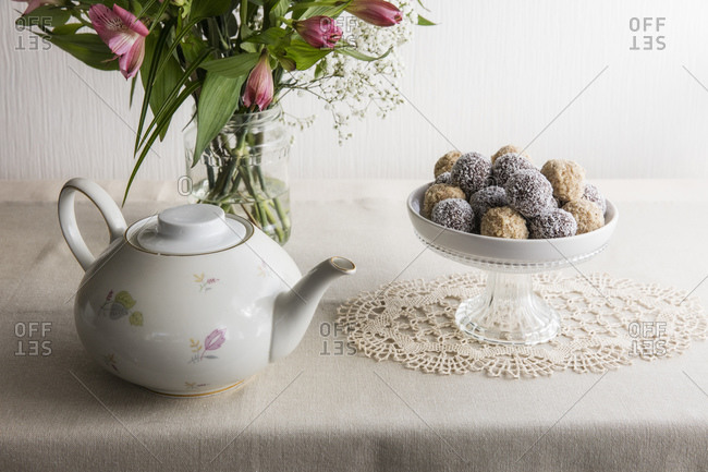 Jar with blooming flowers- bowl of protein balls and white ceramic teapot