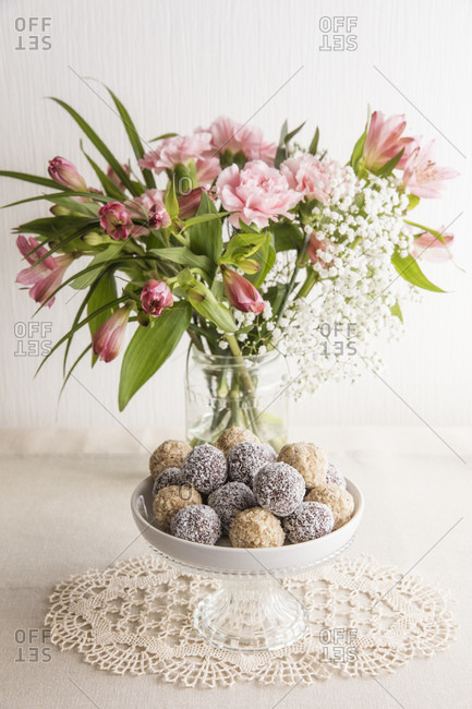 Jar of pink blooming flowers and bowl of protein balls
