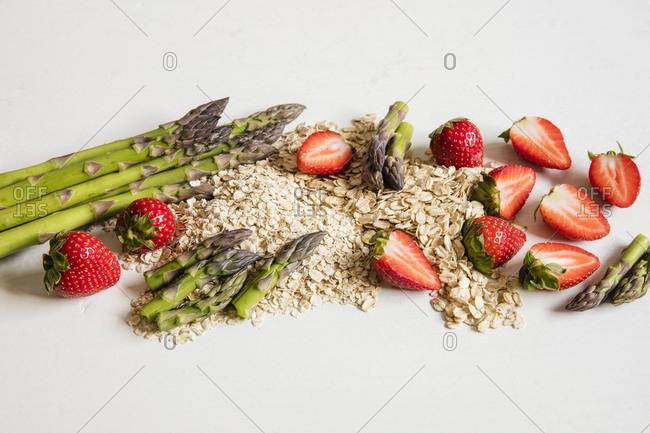Studio shot of oats- asparagus stalks and halved strawberries