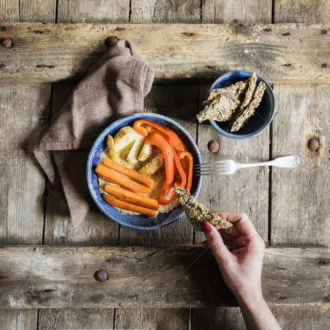 Hand of woman eating bowl of vegan hummus with fried carrots and bell peppers