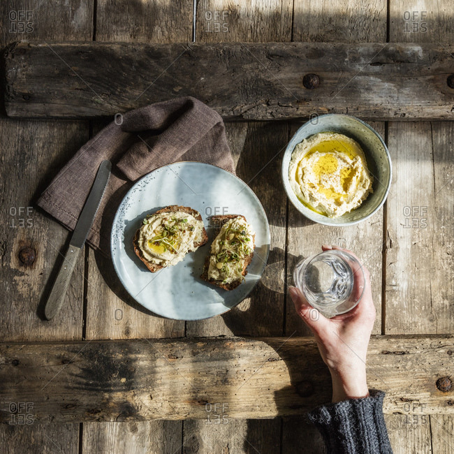 Hand of woman holding glass of water and plate with bread slices with hummus and sprouts