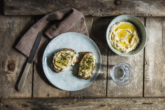 Glass of water and bread slices with hummus and sprouts