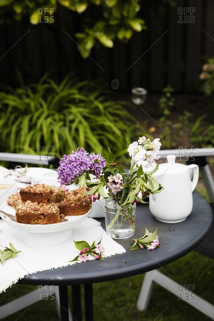 Flower vase and homemade rhubarb cake on garden coffee table