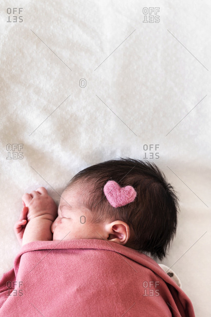 Newborn baby girl with heart shape on head sleeping over bed in hospital