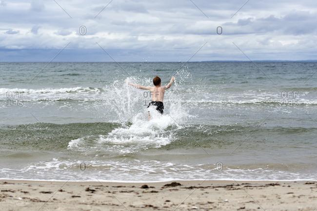 Shirtless boy enjoying splashing of water on beach