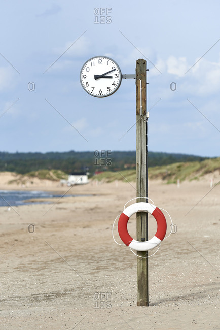 Inflatable tube on clock pole at beach against sky