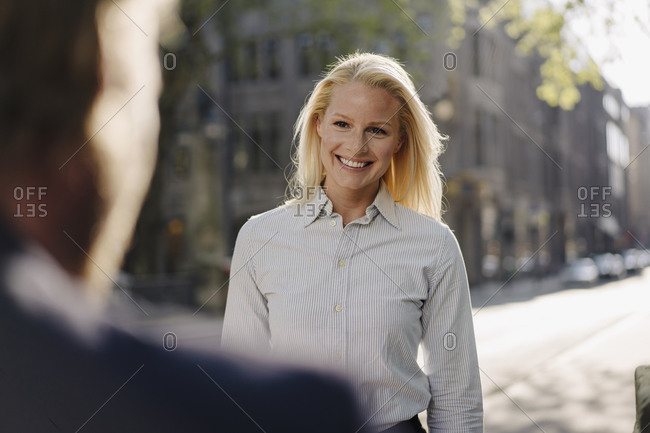 Smiling blond businesswoman looking at male colleague while standing in city
