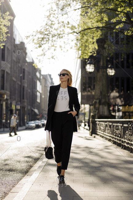Fashionable businesswoman with hand in pocket walking on sidewalk in city