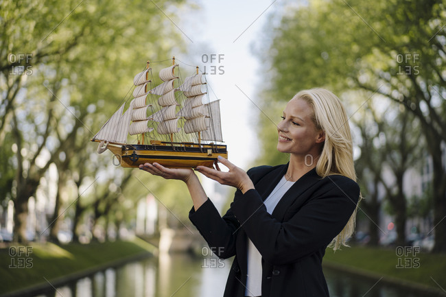 Smiling blond businesswoman looking at model sailboat while standing against canal in city