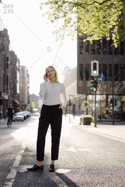 Businesswoman talking through smart phone while standing with hand in pocket on street