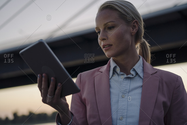 Beautiful businesswoman using digital tablet in city at dusk