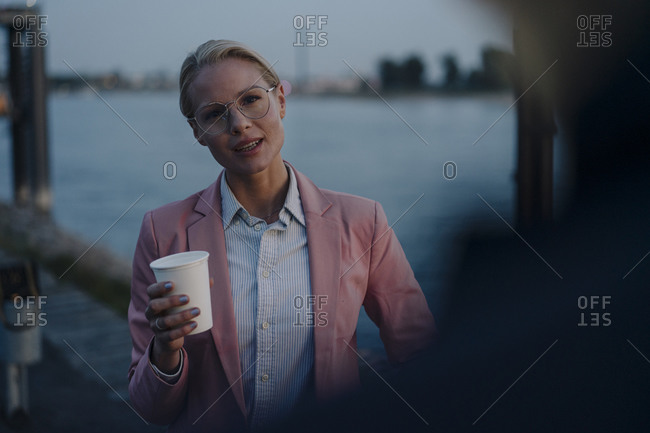 Beautiful businesswoman holding disposable cup while looking at male colleague in city