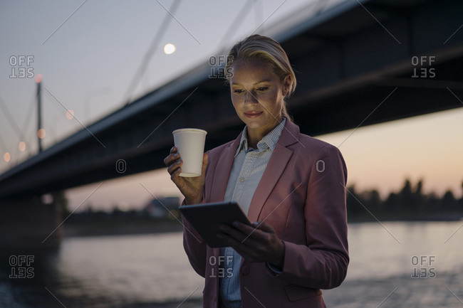 Beautiful businesswoman using digital tablet while holding disposable cup against bridge in city at dusk