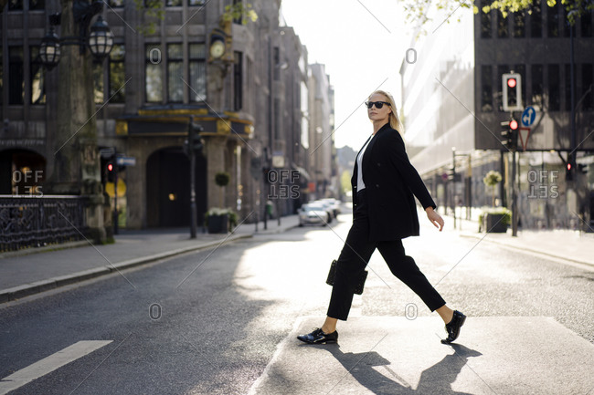 Fashionable female professional crossing street in city
