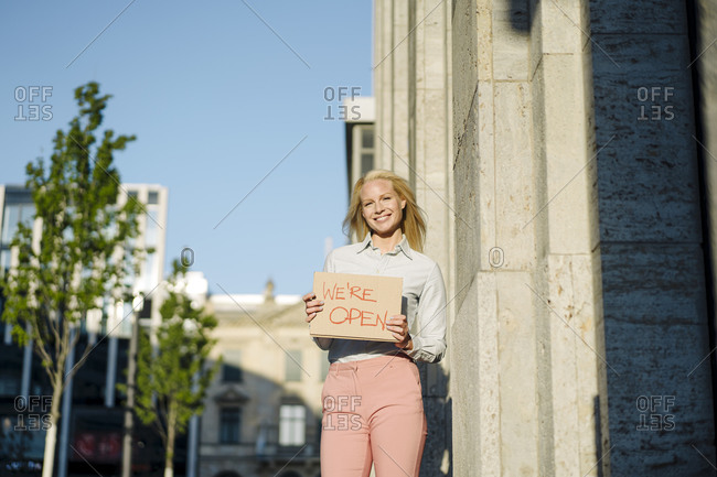 Smiling beautiful businesswoman holding open sign cardboard placard by building in financial district