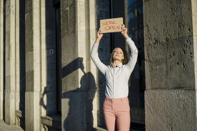 Smiling beautiful businesswoman holding open sign cardboard placard against building in financial district