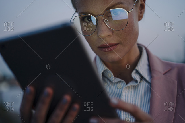 Confident beautiful businesswoman using digital tablet at dusk