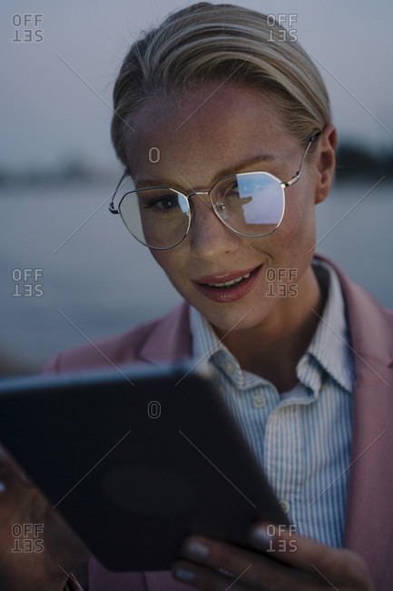 Smiling beautiful female professional using digital tablet at dusk
